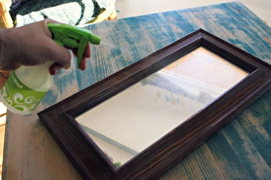spraying homemade glass cleaner